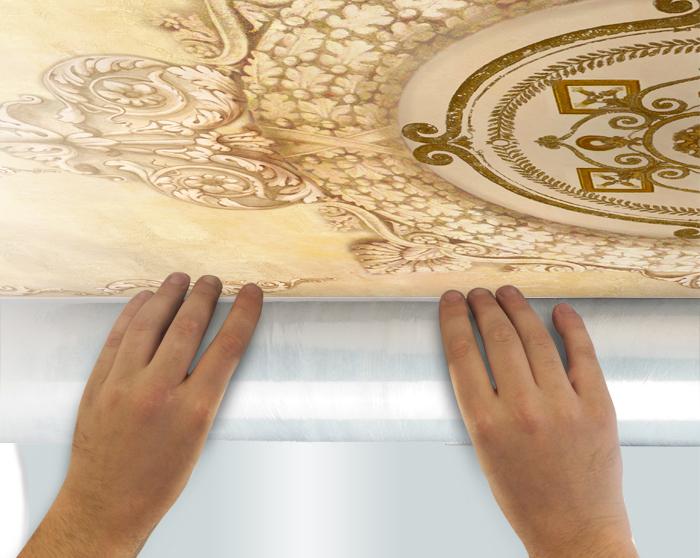 5.Отмотайте примерно 50 см полотна фрески, снимая пленку, и приложите к потолку. Тубус с фреской держите как можно ближе к потолку.